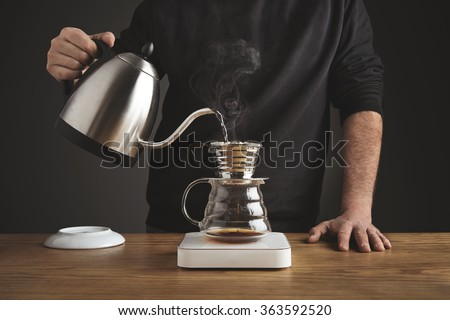 Barista black sweatshirt spills hot water prepare filtered coffee from silver teapot to beautiful transparent chrome drip maker on white simple weights. Everything thick wooden table cafe shop. Steam - stock photo