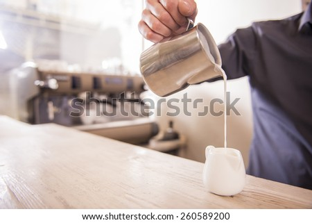 Barista hands is pouring milk making cappuccino. - stock photo