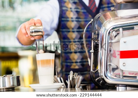 Barista in cafe or coffee bar preparing pouring espresso shot in glass of latte macchiato - stock photo