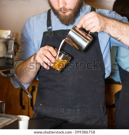 Barista making coffee. Hands of barista making latte or cappuccino coffee pouring milk in cup and making latte art - stock photo