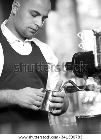 Barista mixing milk on espresso machine for making fresh coffee, Latte and cappuccino. Low light. Small depth of field. Black and white