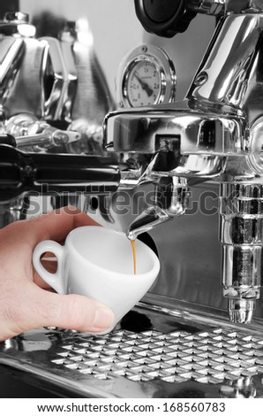 Barista prepares espresso in his coffeeshop; close-up