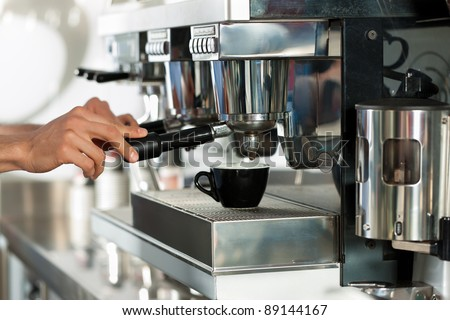 Barista prepares espresso in his coffeeshop; close-up - stock photo