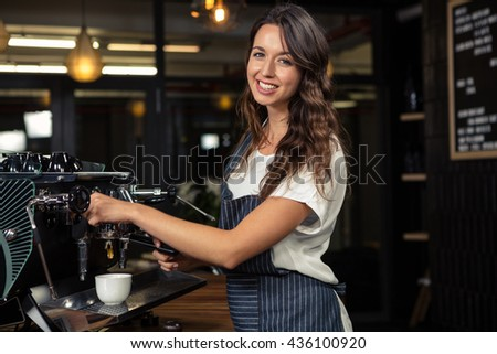 Barista preparing coffee with machine in coffee shop
