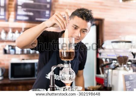 Barista preparing drip coffee in Asian coffee shop using professional machine parts  - stock photo
