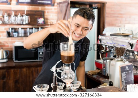 Barista preparing drip coffee in Asian coffee shop using professional machine parts  - stock photo
