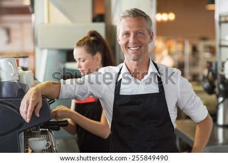 Barista smiling at the camera at the cafe - stock photo
