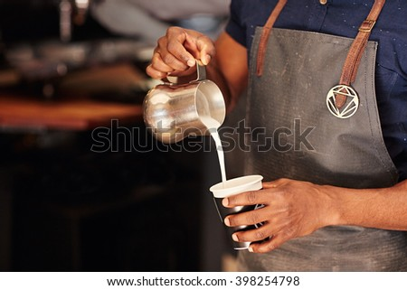 Barista wearing apron pouring milk from metal jug into cup - stock photo