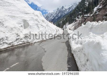 Barlachala pass in Leh Manali Highway, roads through ice walls with snow peak of himalaya in background - stock photo