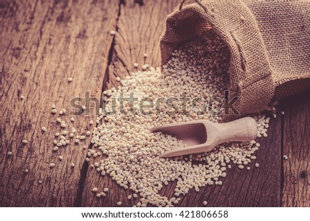 barley beans pour from sack on wood background - stock photo