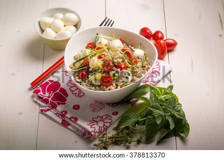 barley salad with mozzarella tomatoes zucchinis and herbs - stock photo