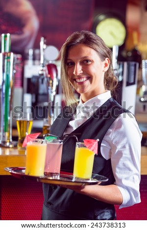 Barmaid holding tray of cocktails in a bar