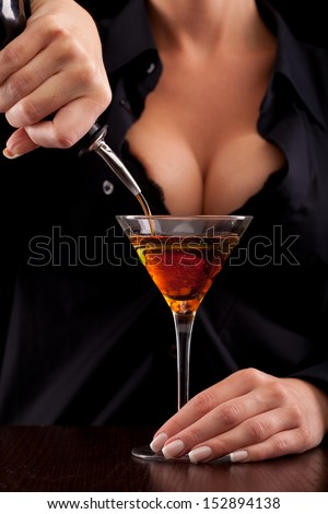 Barmaid stands behind bar mixing drink for client - stock photo