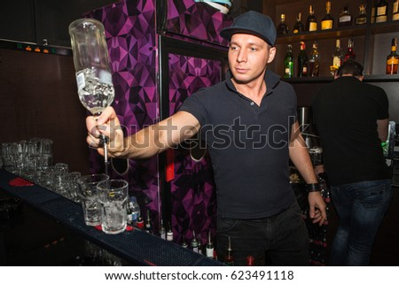 Barman at work in luxury nightclub. Bartender make fun at party time in elite night club at night party.  The barman prepares an alcoholic cocktail with vodka during a night party in a nightclub.