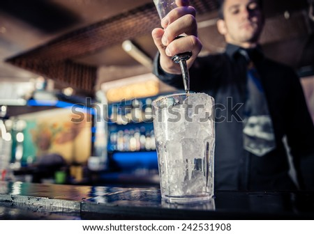 barman at work, pouring spirit into a glass. concept about professions and drinks - stock photo