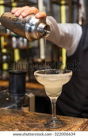 Barman at work, preparing cocktails. Pouring margarita to cocktail glass. concept about service and beverages. - stock photo