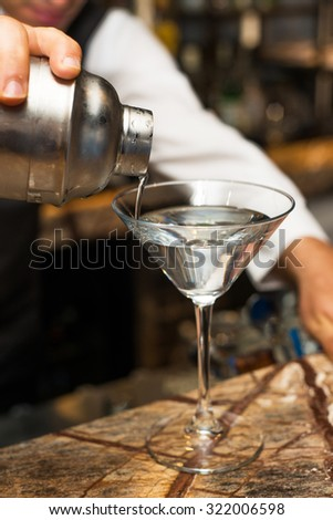 Barman at work, preparing cocktails. pouring martini to cocktail glass. concept about service and beverages. - stock photo