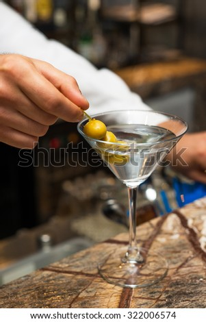 Barman at work, preparing cocktails. Preparing martini with olives. concept about service and beverages.