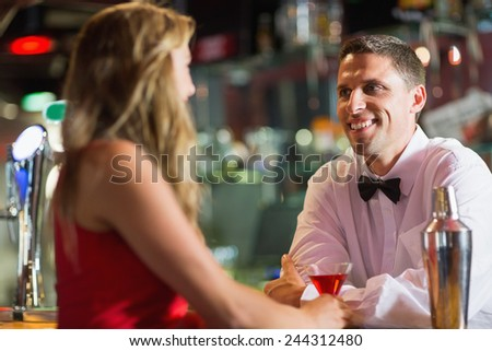 Barman chatting to pretty customer in a bar - stock photo