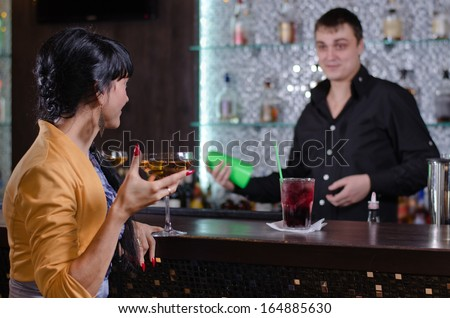 Barman chatting with an elegant female customer as she sits at the bar enjoying a cocktail