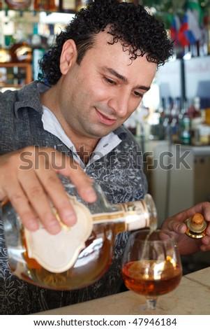 Barman fills glass. Smiling man against shelves with bottles. - stock photo