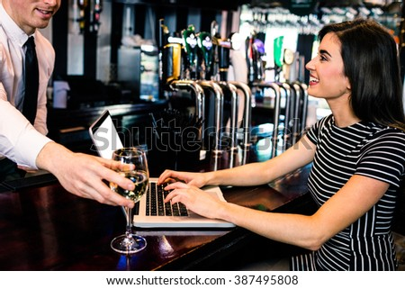 Barman giving a glass of wine at woman using laptop in a bar - stock photo