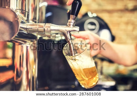 barman hand at beer tap pouring a draught lager beer serving in a restaurant or pub. Vintage soft effect on photo - stock photo
