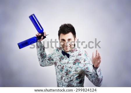 barman holding shaker and blue bottle - stock photo