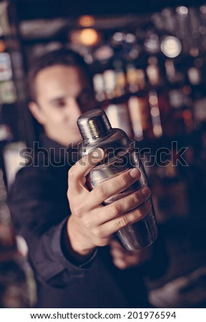 Barman In Pub Holding Shaker. Focus Is On Shaker. - stock photo
