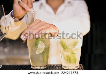 Barman is decorating a cocktail