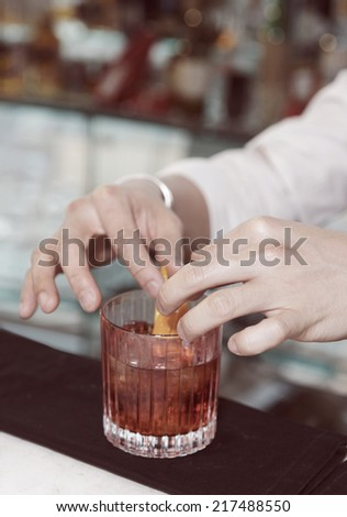Barman is decorating cocktail with lemon zest, toned image - stock photo