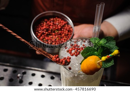 Barman is decorating cocktail with pink pepper - stock photo
