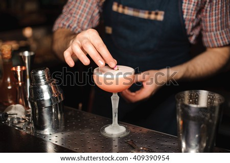 Barman is decorating cocktail with rose no face - stock photo
