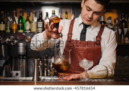 Barman is making a cocktail - stock photo