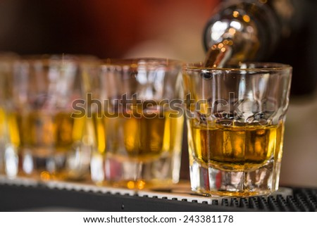 Barman makes whisky shot drinks in row. Alcoholic shots in nightclub - stock photo