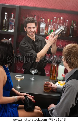Barman making cocktail for young couple at the bar - stock photo