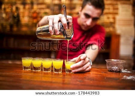 barman mixing and pouring a summer alcoholic cocktail into small glasses on counter