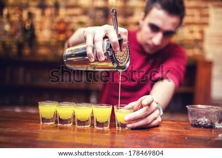 barman mixing and pouring a summer alcoholic cocktail into small glasses on counter - stock photo