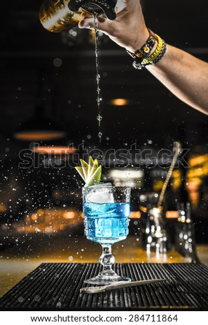 Barman pouring a cocktail into a glass at night club - stock photo