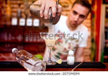 barman pouring a margarita alcoholic cocktail served in casino and bar - stock photo