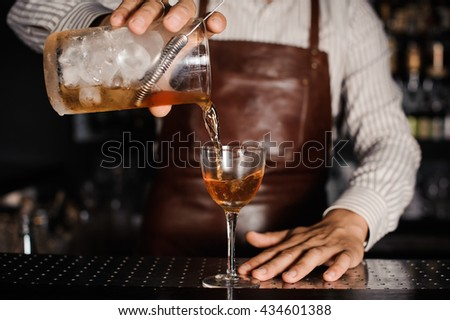 barman pouring alcoholic cocktail in glass