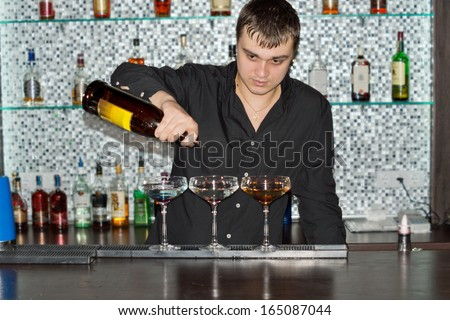 Barman pouring drinks at a bar into three elegant cocktail glasses as he prepares an exotic blend - stock photo
