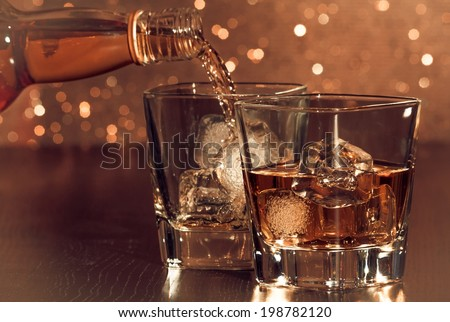 barman pouring whiskey behind whiskey glass on gold bokeh - stock photo
