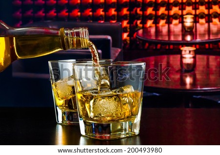 barman pouring whiskey in a lounge bar on wood table - stock photo