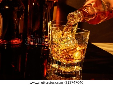 barman pouring whiskey in front of whisky glass and bottles on black table - stock photo