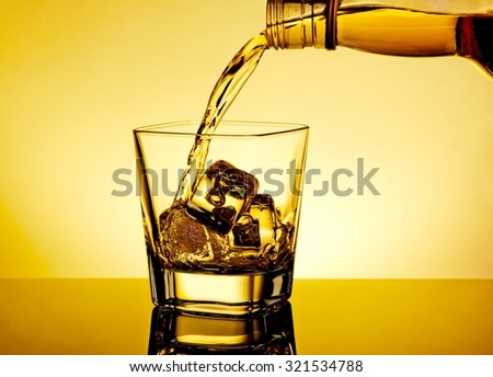 barman pouring whiskey in the glass on table with reflection, warm tint atmosphere, warm tint atmosphere, time of relax with whisky - stock photo
