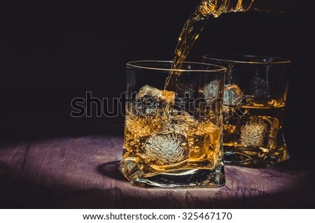 barman pouring whiskey in two glasses on wood table, warm atmosphere, old style, time of relax with whisky with space for text - stock photo