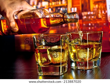 barman pouring whiskey on bar table lounge bar atmosphere - stock photo