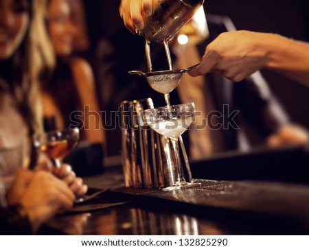 Barman pouring wine from shaker and serving it - stock photo