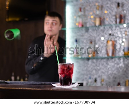 Barman serving a customer in a nightclub looking round attentively as someone places an order for a drink